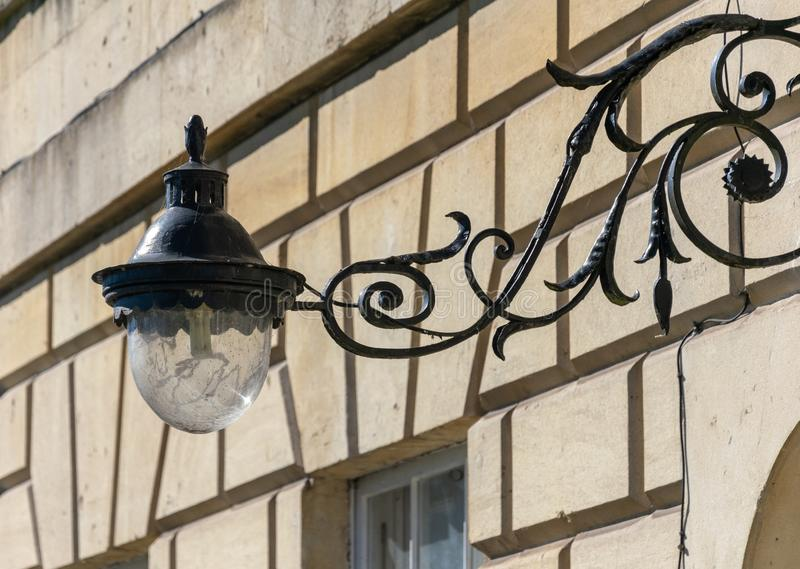 Lampada decorata del ferro battuto sul sostegno di lampada sulla facciata di una casa nel bagno fotografia stock