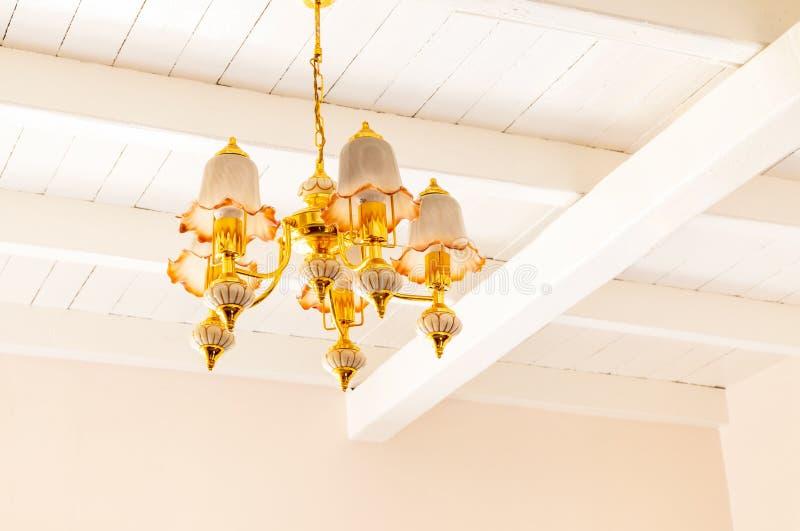 Lampada del candeliere sul soffitto Luce dorata del candeliere nella stanza bianca Annata e contemporaneo eleganti decorativi immagine stock