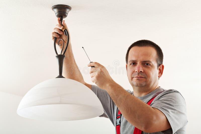 Lampada del soffitto del montaggio dell'elettricista immagine stock libera da diritti