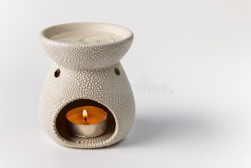 Lampada dell'aroma con una candela bruciante su fondo bianco immagine stock libera da diritti