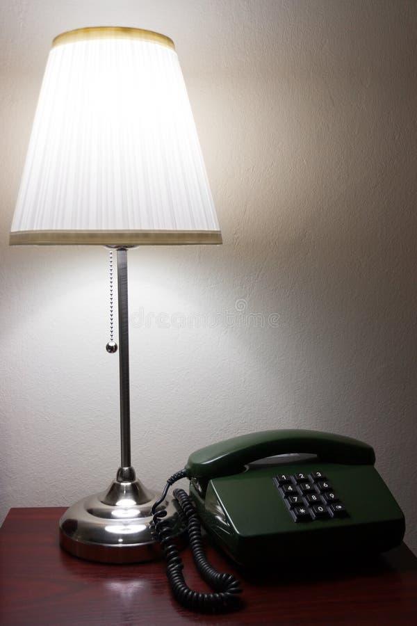 Lampada dell'hotel e un telefono su mobilia rossastra immagine stock