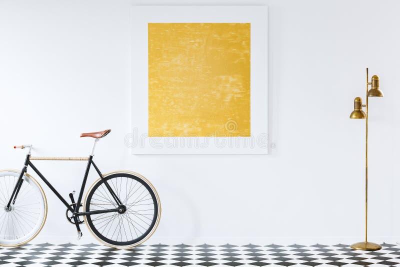 Lampada dell'oro e bici nera sul pavimento della scacchiera in anticamera inter fotografia stock libera da diritti