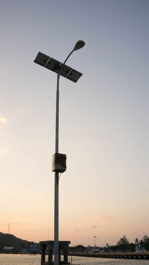 Lampada della luce della torre del pannello solare con il fondo giallo del cielo di luce solare o di alba immagine stock libera da diritti