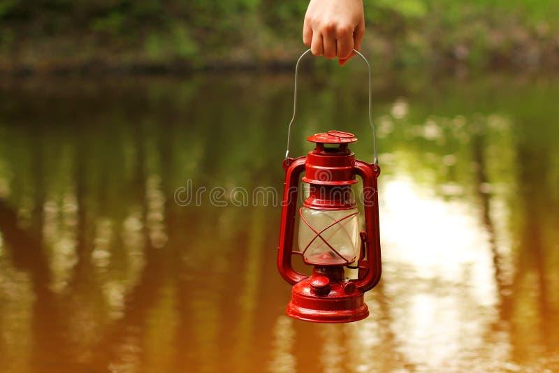 Lampada di cherosene a disposizione contro lo sfondo del fiume fotografie stock