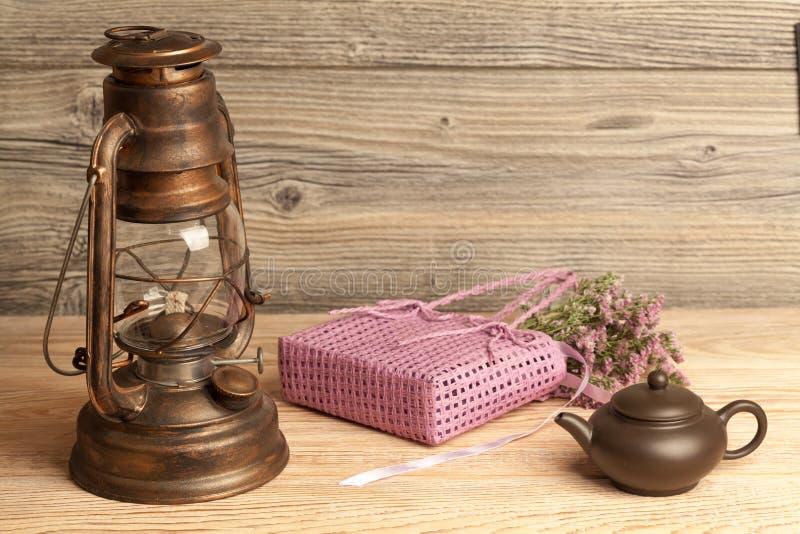 Lampada di cherosene, teiera, fiori e borsa su legno immagine stock libera da diritti