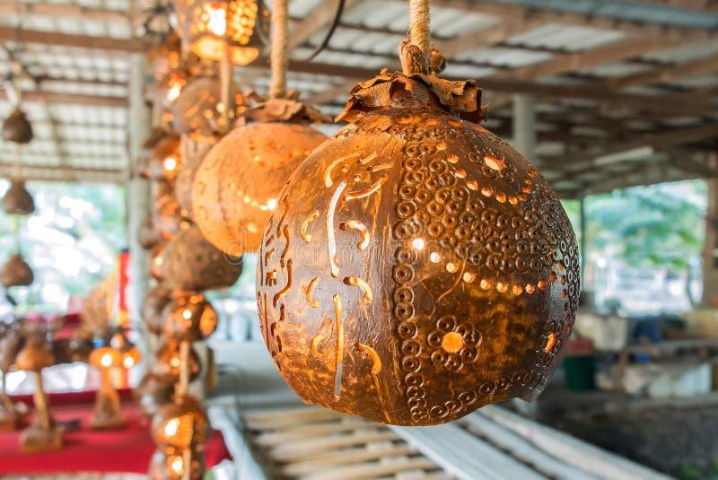 Lampada di legno scolpita classico illuminata fatta dalla noce di cocco asciutta che pende dal soffitto fotografie stock libere da diritti
