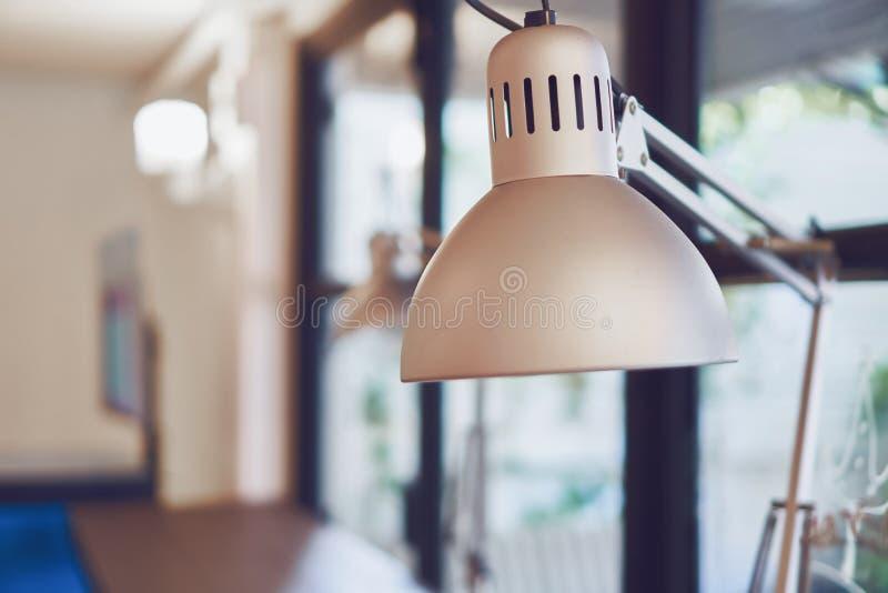 Lampada di scrittorio grigia d'annata sulla tavola in caffè del caffè fotografia stock libera da diritti