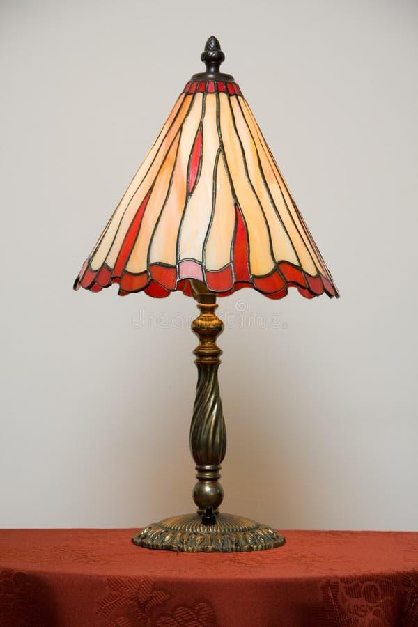 Lampada di vetro macchiato sulla tabella immagine stock