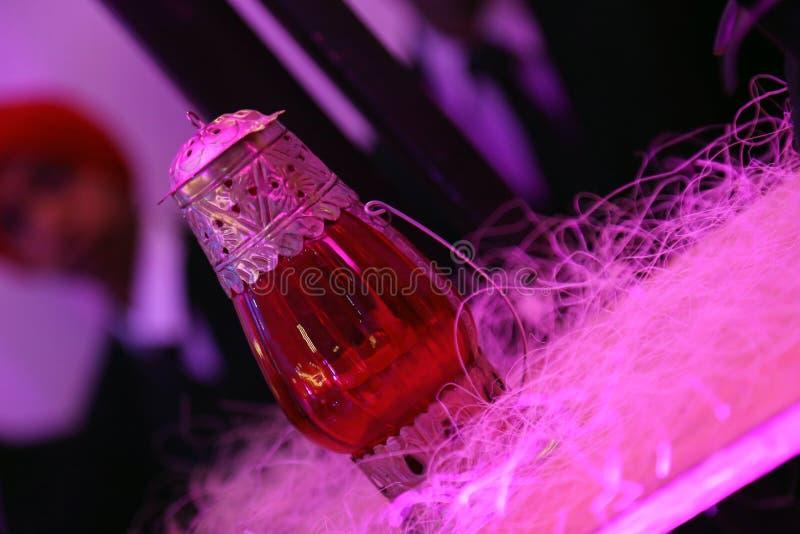 Lampada di vetro rossa con il lavoro del metallo isolato con il fondo della sfuocatura fotografia stock