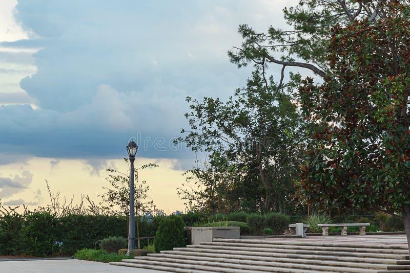 Lampada di via sul pendio di collina con le scale, la pianta del banco e le grandi nuvole immagine stock libera da diritti