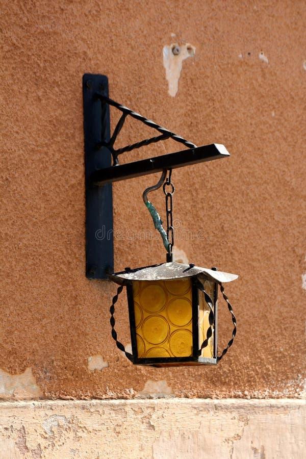 Lampada di via di vetro gialla di vecchio stile barrocco sul bordo della parete abbandonata incrinata dilapidata della casa immagini stock libere da diritti