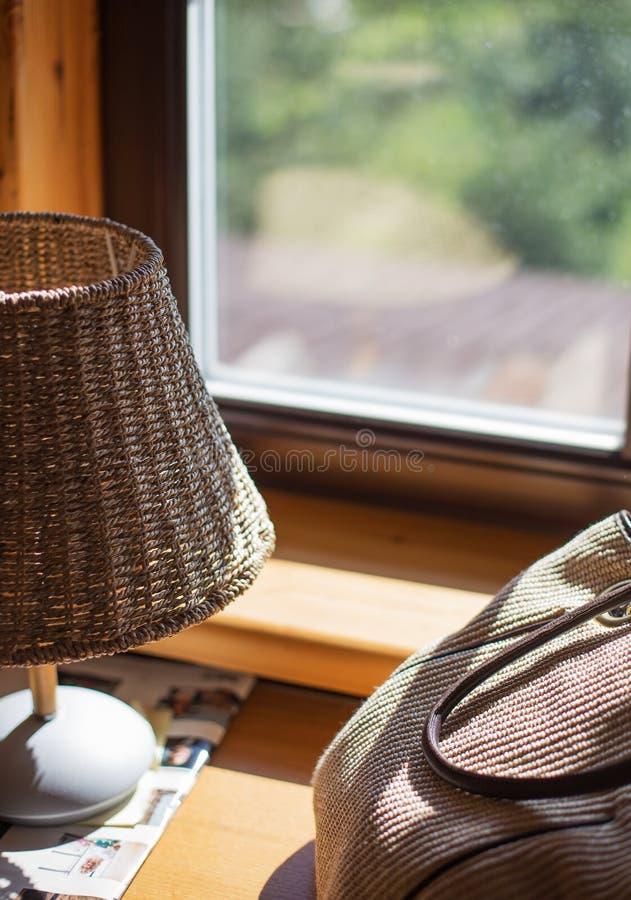 Lampada e borsa della paglia sulla finestra immagini stock