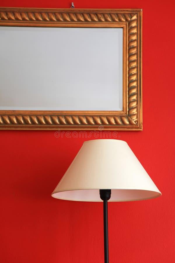 Lampada e specchio incorniciato sulla parete alla moda rossa fotografie stock libere da diritti