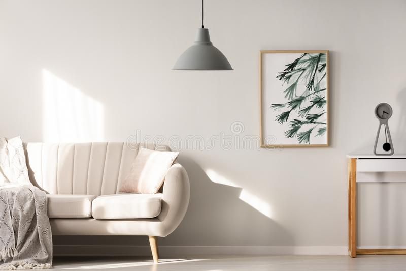 Lampada grigia nell'interno luminoso del salone con il manifesto accanto al bei fotografia stock libera da diritti