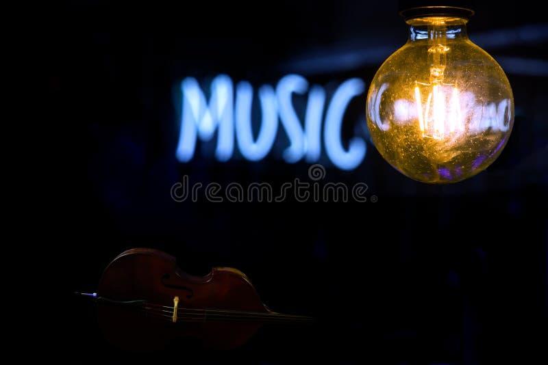 Lampada incandescente elettrica sui precedenti dell'iscrizione al neon mezzo vaga di musica con un contrabbasso qui sotto fotografia stock libera da diritti