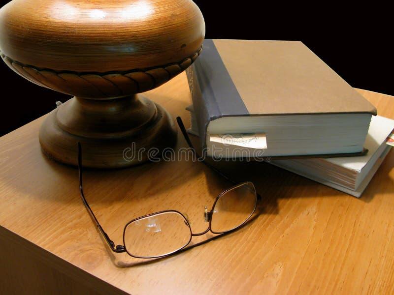 Lampada, libro & vetri di Nightstand fotografia stock libera da diritti