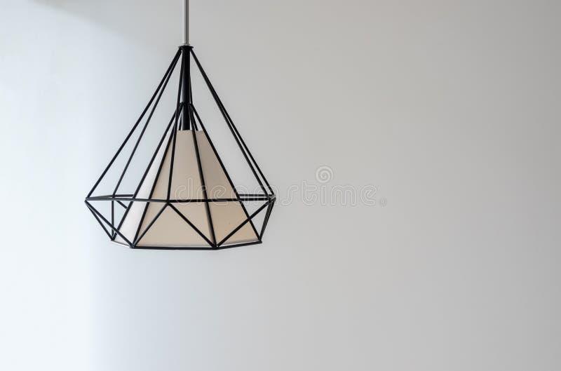 Lampada moderna che pende giù dal soffitto sul fondo bianco della parete immagine stock libera da diritti