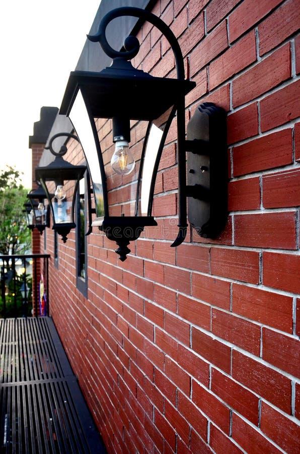 Lampada nera del metallo sul muro di mattoni con la scalata fotografia stock