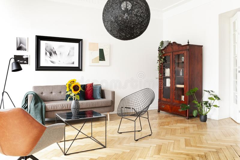 Lampada nera sopra la poltrona e la tavola nell'interno luminoso del salone con il manifesto e le piante Foto reale fotografia stock