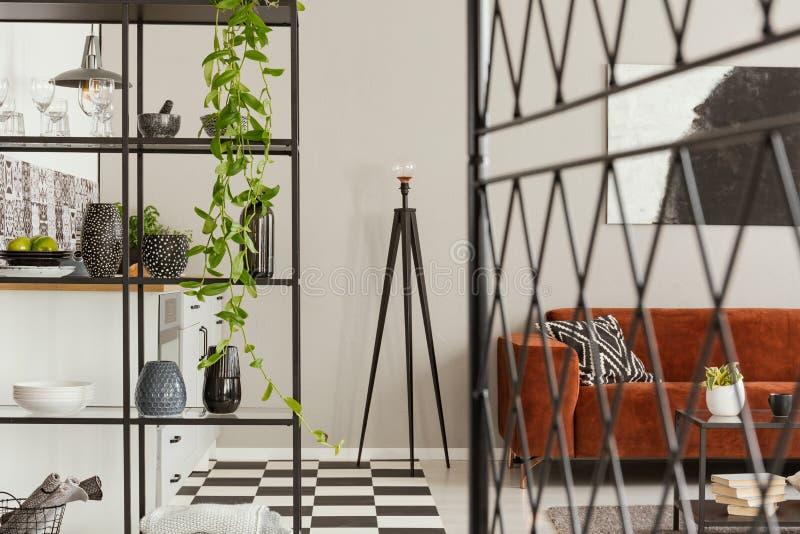 Lampada operata del metallo in mezzo alla cucina alla moda con mobilia industriale e lo strato marrone del velluto fotografie stock libere da diritti