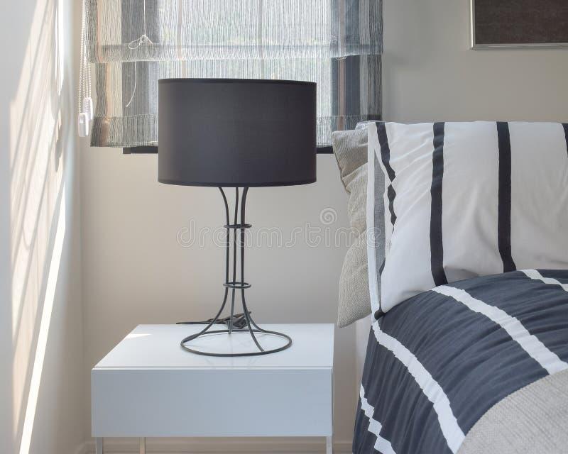 Lampada pronta con la lampada nera di ombreggiatura sul comodino con la lettiera del modello a strisce fotografia stock