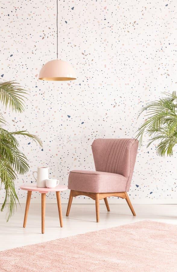 Lampada rosa sopra la tavola e la poltrona di legno in salone pastello fotografia stock libera da diritti