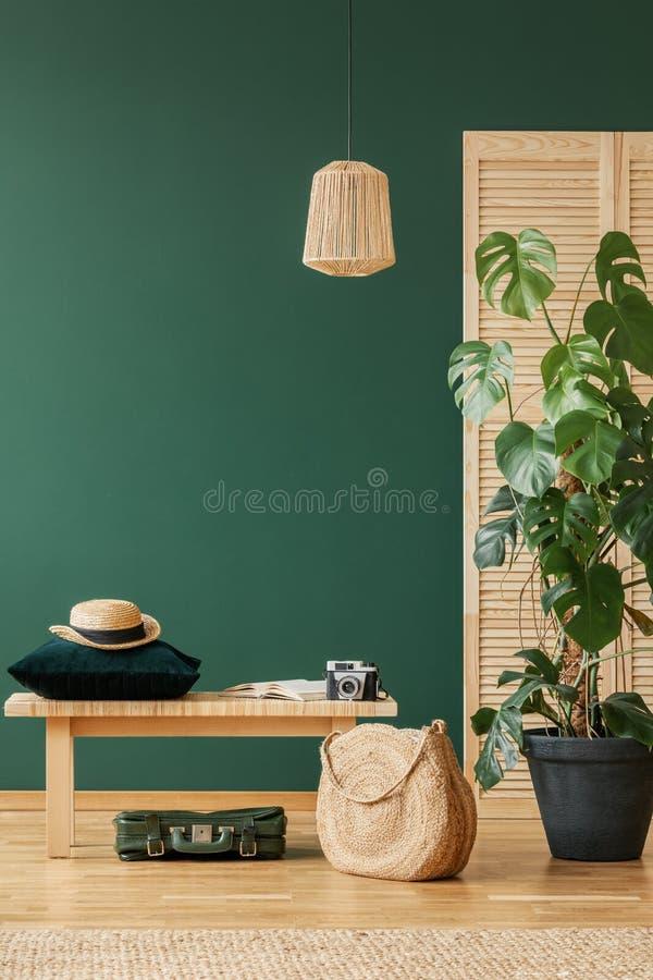 Lampada sopra il panchetto di legno e borsa nell'interno piano verde con il cappello Foto reale fotografia stock libera da diritti