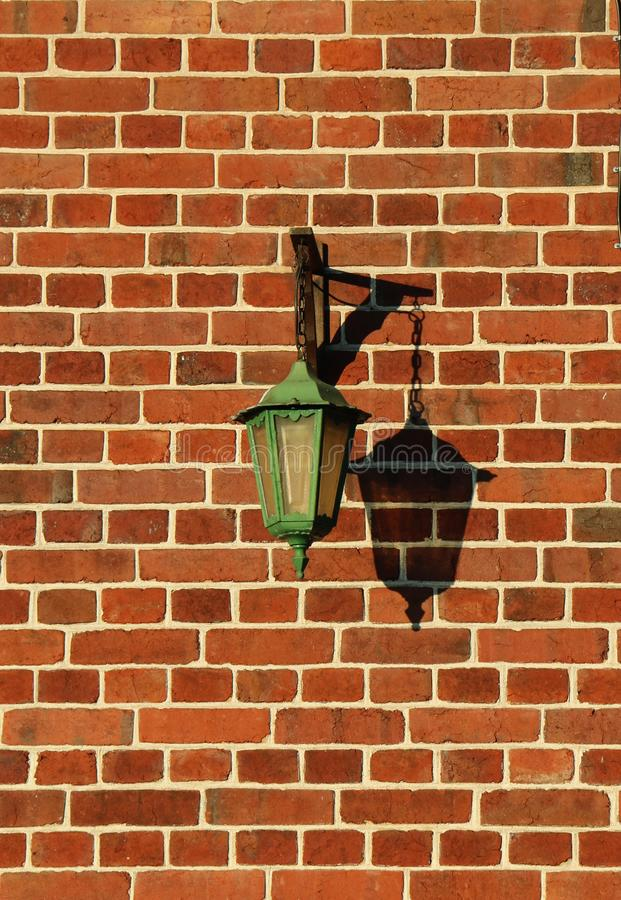 Lampadaire normand sur mur en briques rouges. Old green street lamp on the red brick wall of a house located in Normandy, France royalty free stock image