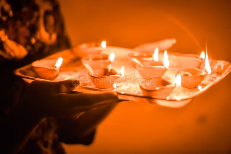 Lampade di festival di Diwali a disposizione, Dipawali felice, diwali indiano di festival Mani femminili che tengono lampada a ol fotografia stock libera da diritti
