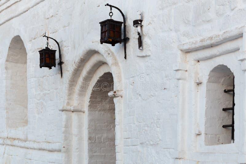 Lampade di via forgiate del ferro sul muro di mattoni bianco dello stucco con le finestre dell'arco fotografia stock