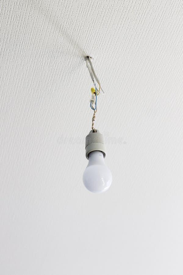 Lampadina bianca che pende dal soffitto bianco immagine stock