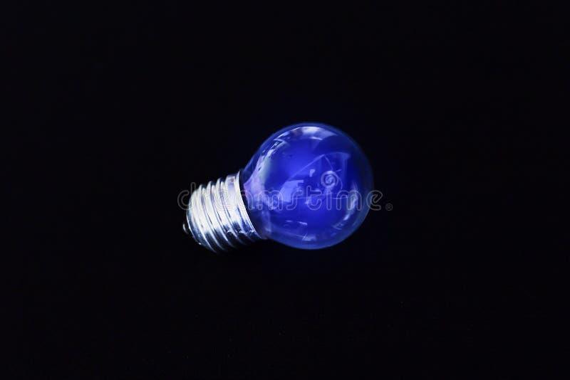 Lampadina blu elettrica su fondo nero fotografia stock