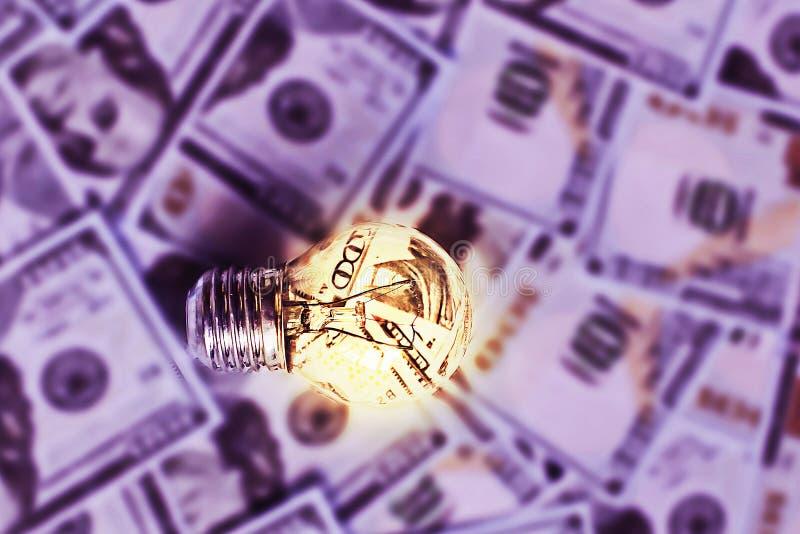 Lampadina bruciante sul fondo dei dollari, elettricità costosa fotografia stock