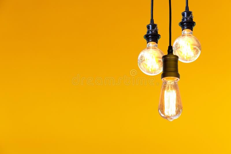 Lampadina d'annata che appende sopra il fondo giallo, concetto di idea fotografia stock libera da diritti