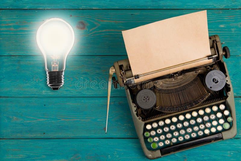 Lampadina d'annata e macchina da scrivere di concetto di idea fotografia stock libera da diritti