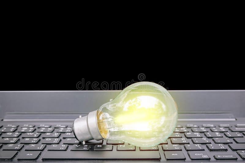 Lampadina del primo piano sul computer portatile della tastiera, lampadine con il nuovo concetto di idee, dell'innovazione, di is fotografia stock libera da diritti
