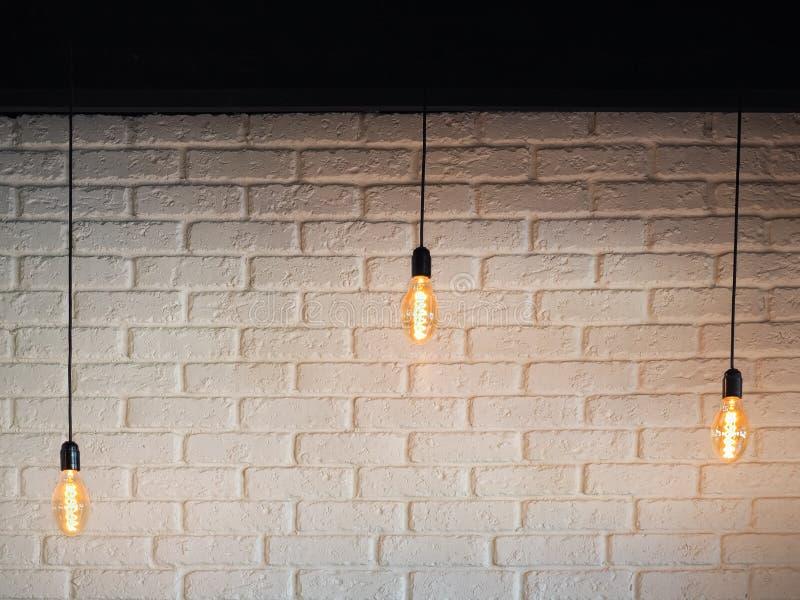 Lampadina elettrica di vecchia illuminazione, retro lampada su un fondo di un muro di mattoni bianco Lampadina di Edison che appe fotografia stock libera da diritti