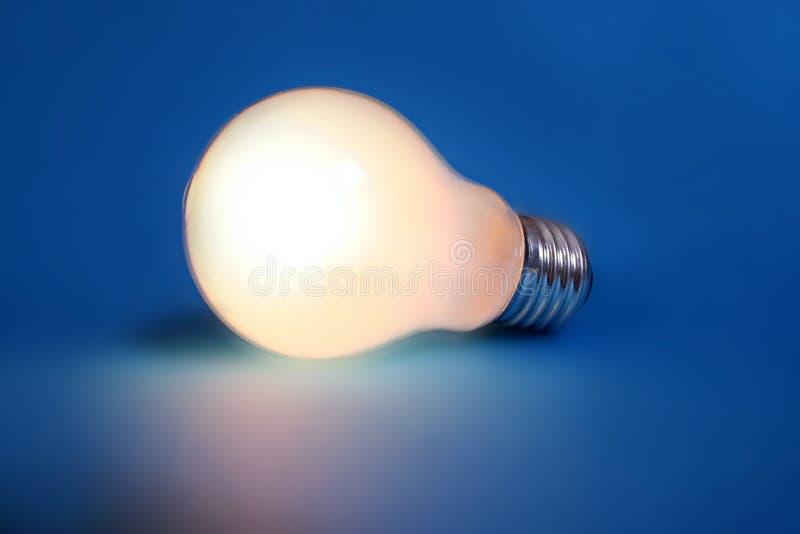 Lampadina illuminata su priorità bassa blu fotografia stock libera da diritti