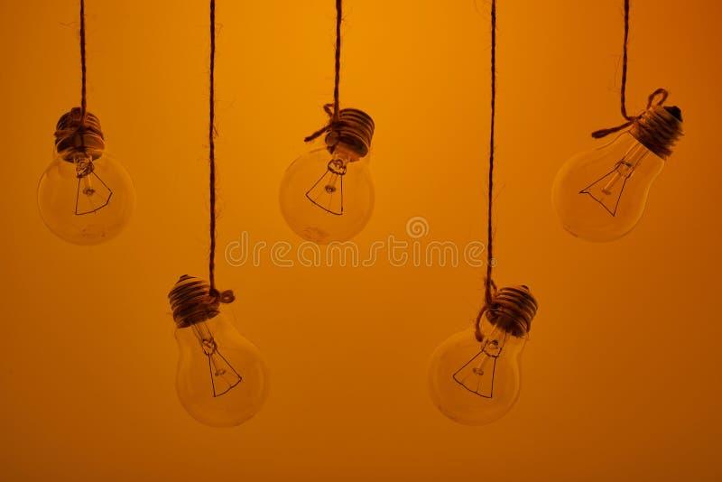 Lampadine della luce a incandescenza che appendono su un fondo giallo fotografia stock