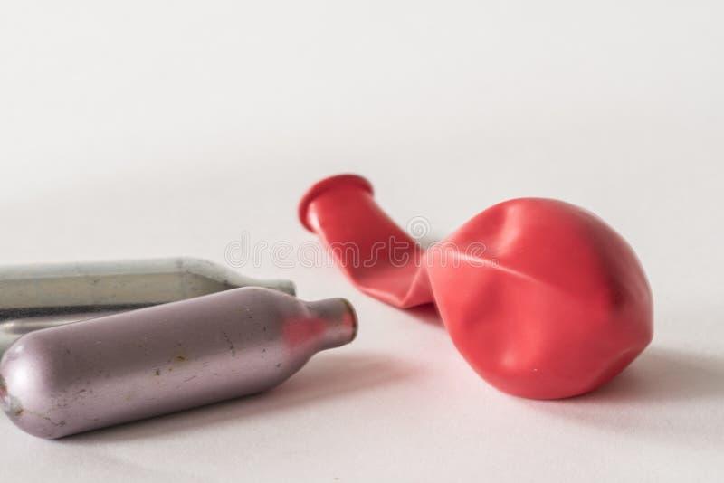 Lampadine e palloni del metallo per gas esilarante, con soldi e lo stetoscopio immagini stock libere da diritti