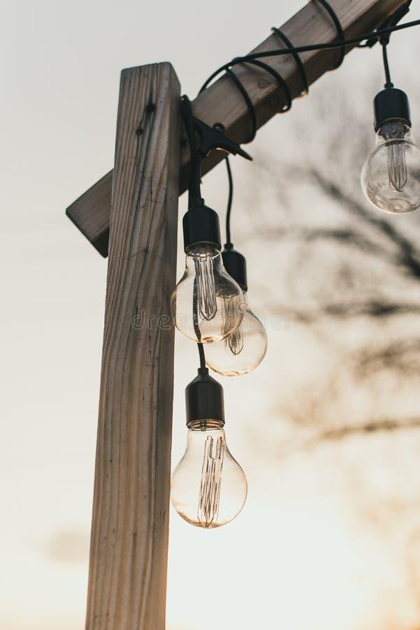 Lampadine nella via nella luce del giorno Una ghirlanda delle lampadine su un piedistallo di legno nel pomeriggio al sole all'ape immagine stock