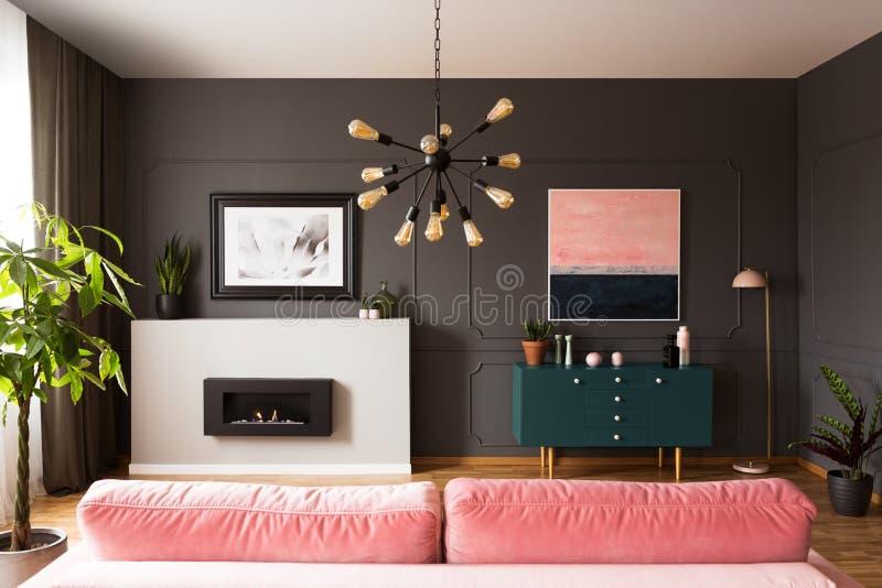Lampan ovanför rosa färger uttrycker i grå lägenhetinre med det gröna kabinettet och spisen royaltyfri fotografi