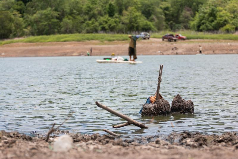 Lampang, Thailand - July 28, 2019 Fishermen can`t fish because of drought. at Land with dry and cracked ground because dryness glo. Fishermen throw a net but can stock photo
