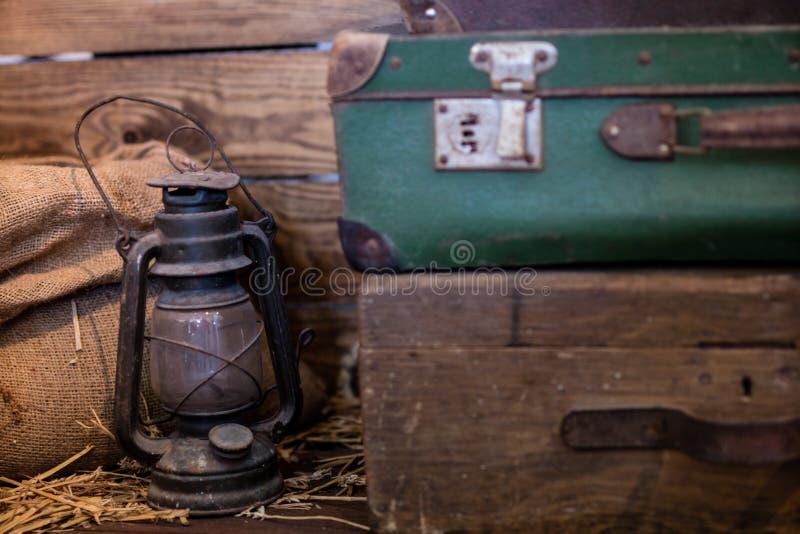 Lampe à pétrole et vieille valise Source lumineuse dans une vieille salle photographie stock