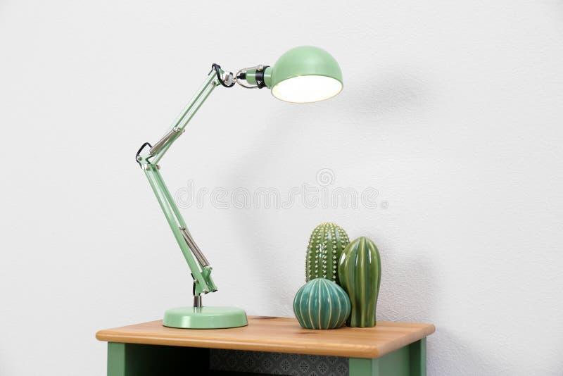 Lampe élégante et cactus décoratifs sur la table image libre de droits
