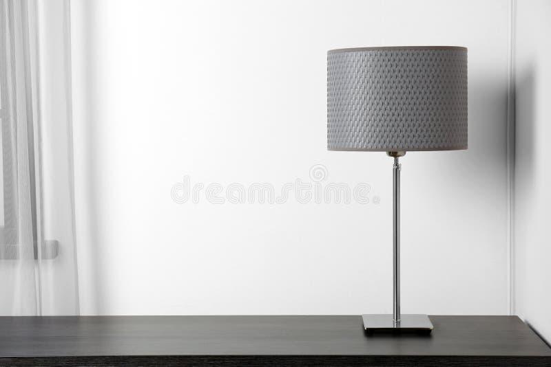 Lampe élégante sur la table près du mur blanc images libres de droits