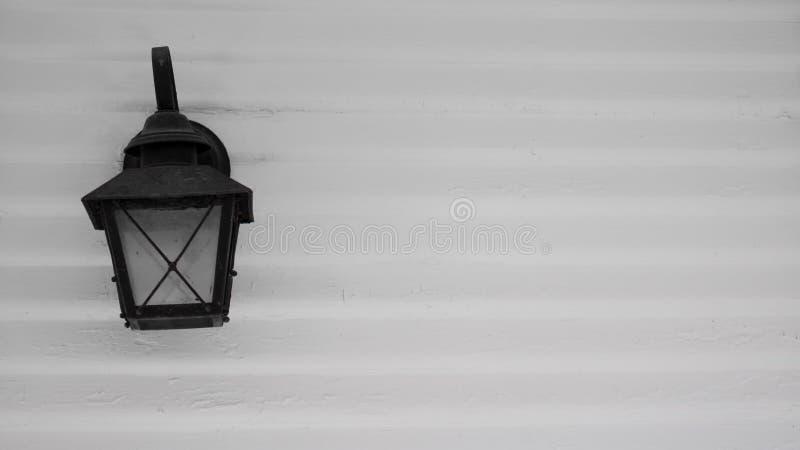 Lampe électrique noire dénommée après des réverbères de gaz de cru, contre un mur de construction extérieur blanc des lamelles en image stock