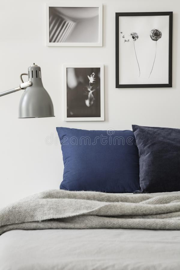 Lampe über grauer Decke auf Bett mit Kissen im minimalen Schlafzimmerinnenraum mit Poster Reales Foto lizenzfreies stockfoto