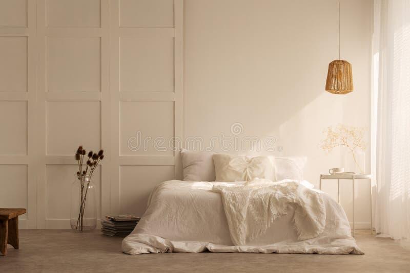 Lampe über weißem Bett mit Kissen im minimalen Schlafzimmerinnenraum mit Anlagen und Schemel stockbilder