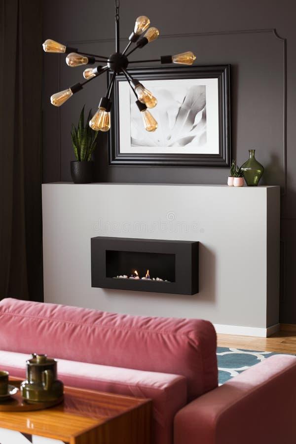 Lampe au-dessus de canapé rose dans l'intérieur moderne gris de salon avec l'affiche au-dessus de la cheminée photos stock